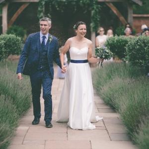 Bride and groom walk the lavendar edged aisle at Upton Barn