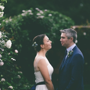 Bride and Groom look into each others eyes by the flowers on the wall in the garden at Upton Barn