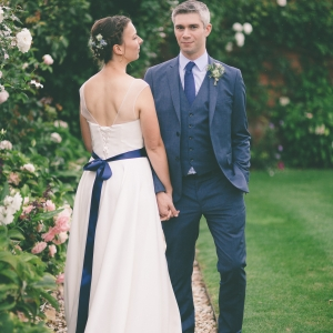 Brides show off back of her dress with groom in the Walled Garden at Upton