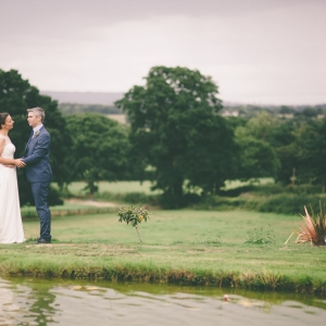 Bride and Groom embrace by the lake surrounded by the Blackdown Hills at Upton Barn