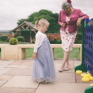 Flower girl plays giant connect four with grandmother in the Walled Garden at Upton