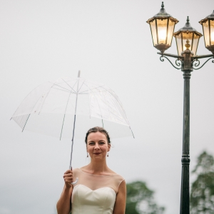 Bride stands underneath a clear umbrella by an old fashioned lamp post at Upton Barn