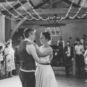 Bride and Groom take their first dance surrounded by guests in the Cider Barn at Upton Barn