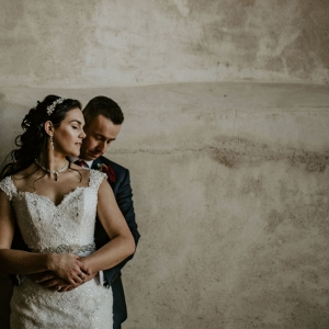 Groom embraces bride by textured wall in the cider barn