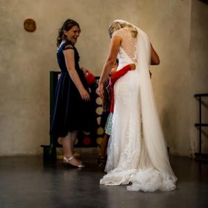 Bride in ornate dress is cuddled by little girl