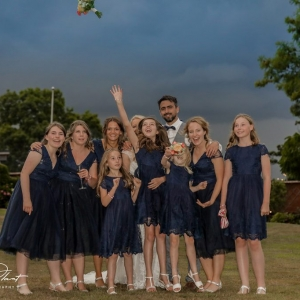 Bridesmaid reaches for flying bouquet