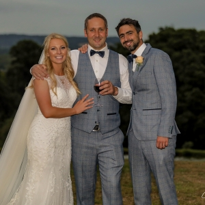 Bride, groom and guset by the lake