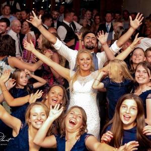 Bride and groom arms wide open on packed dancefloor