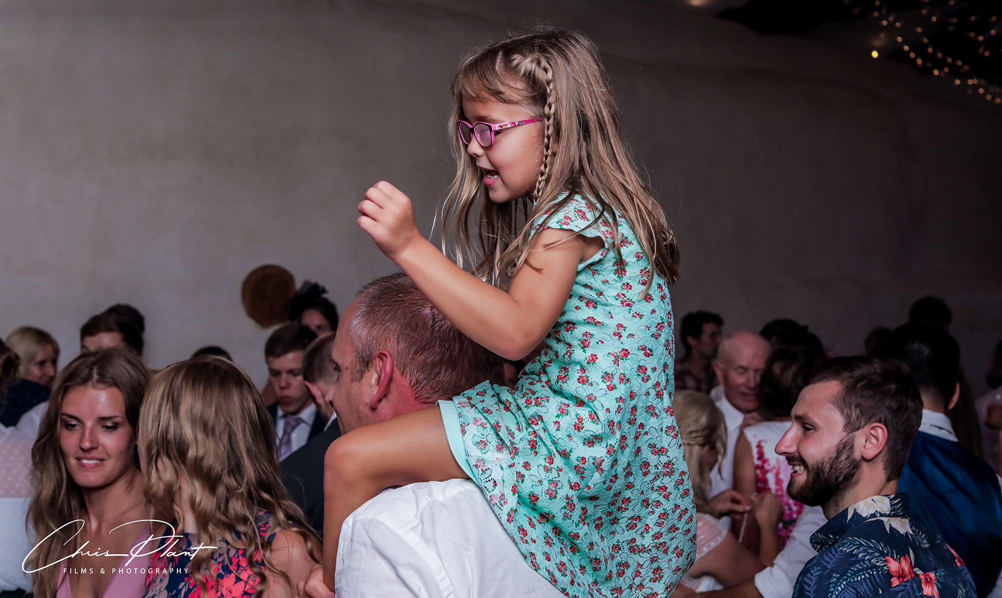 Yound girl on her dads shoulders on the packed dancefloor