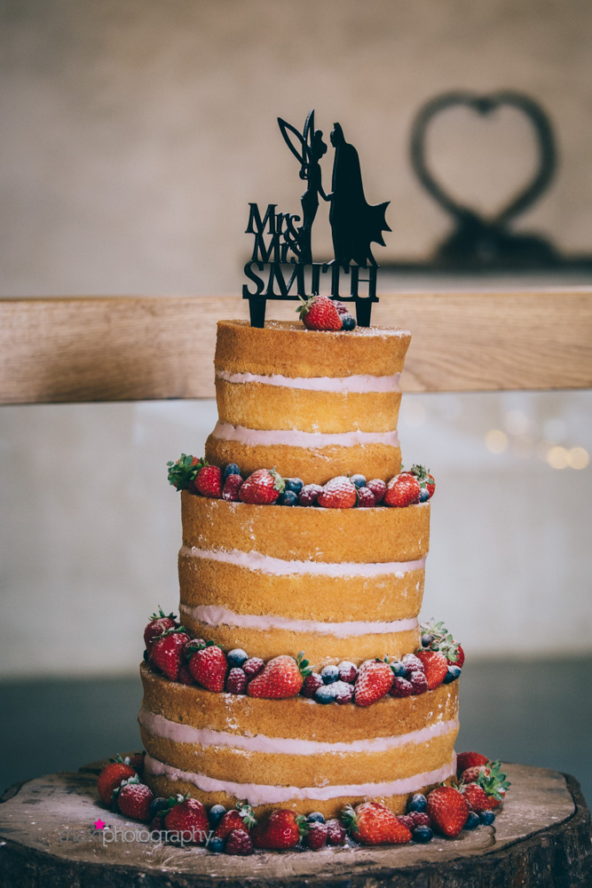Tinkerbell and batman silhouettes adorn naked wedding cake
