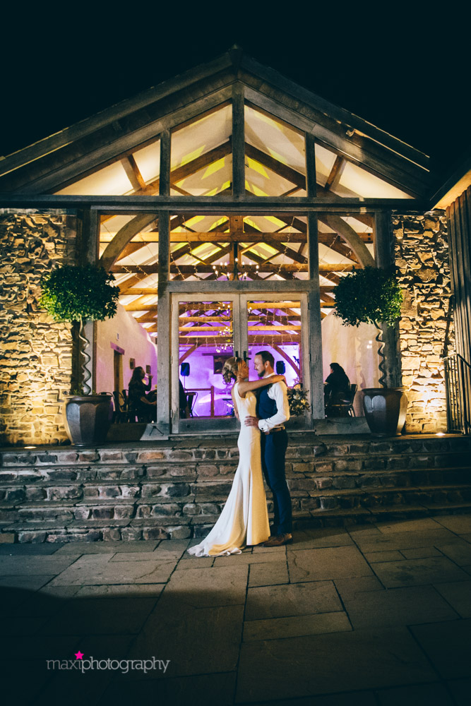 Couple embrace in front of Cider Barn