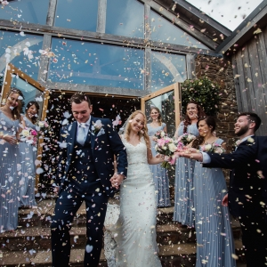 Bride and groom showered in confetti on Cider Barn steps