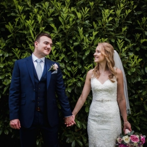 Bride and groom hold hands infrom of green leaf wall