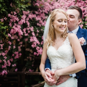 Couple embrace in front of floral background