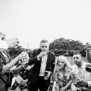 Wedding guests drinking shots in the garden