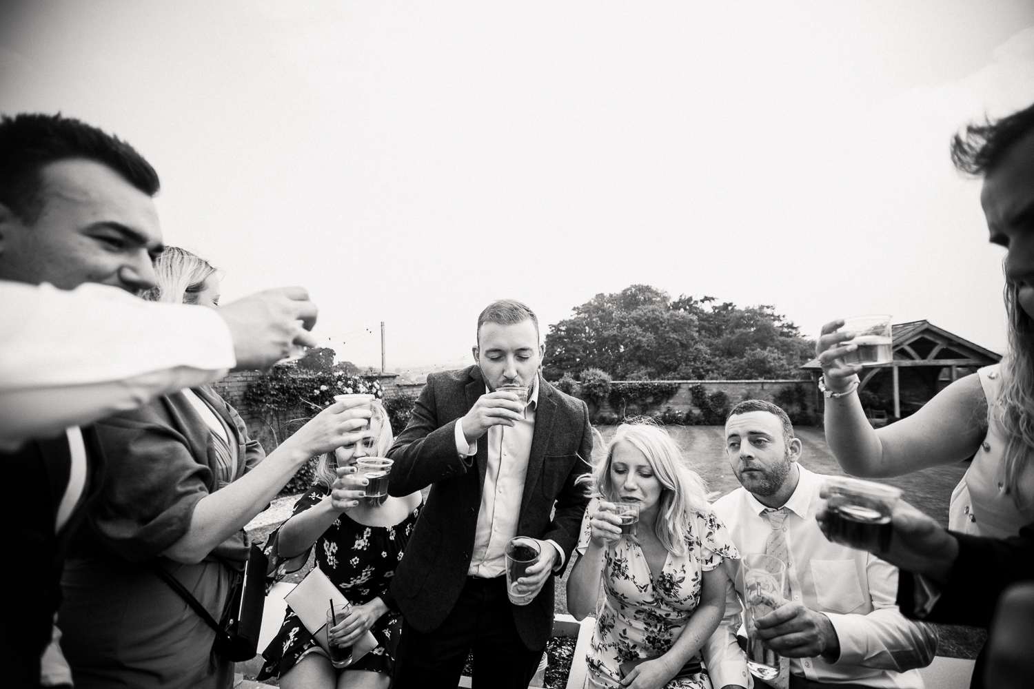 Wedding guests drinking shots in the garden