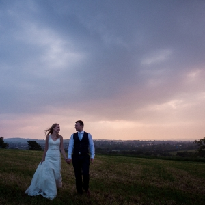 Bride and groom walking in a field at dusk