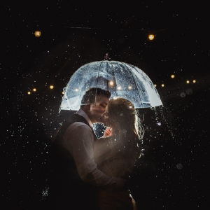 Bride and groom kiss under clear umbrella in the rain