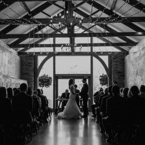 Bride and groom silhouetted by the cider barn window exchanging vows