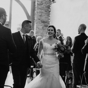 Bride and groom walk hand-in-hand back up the aisle