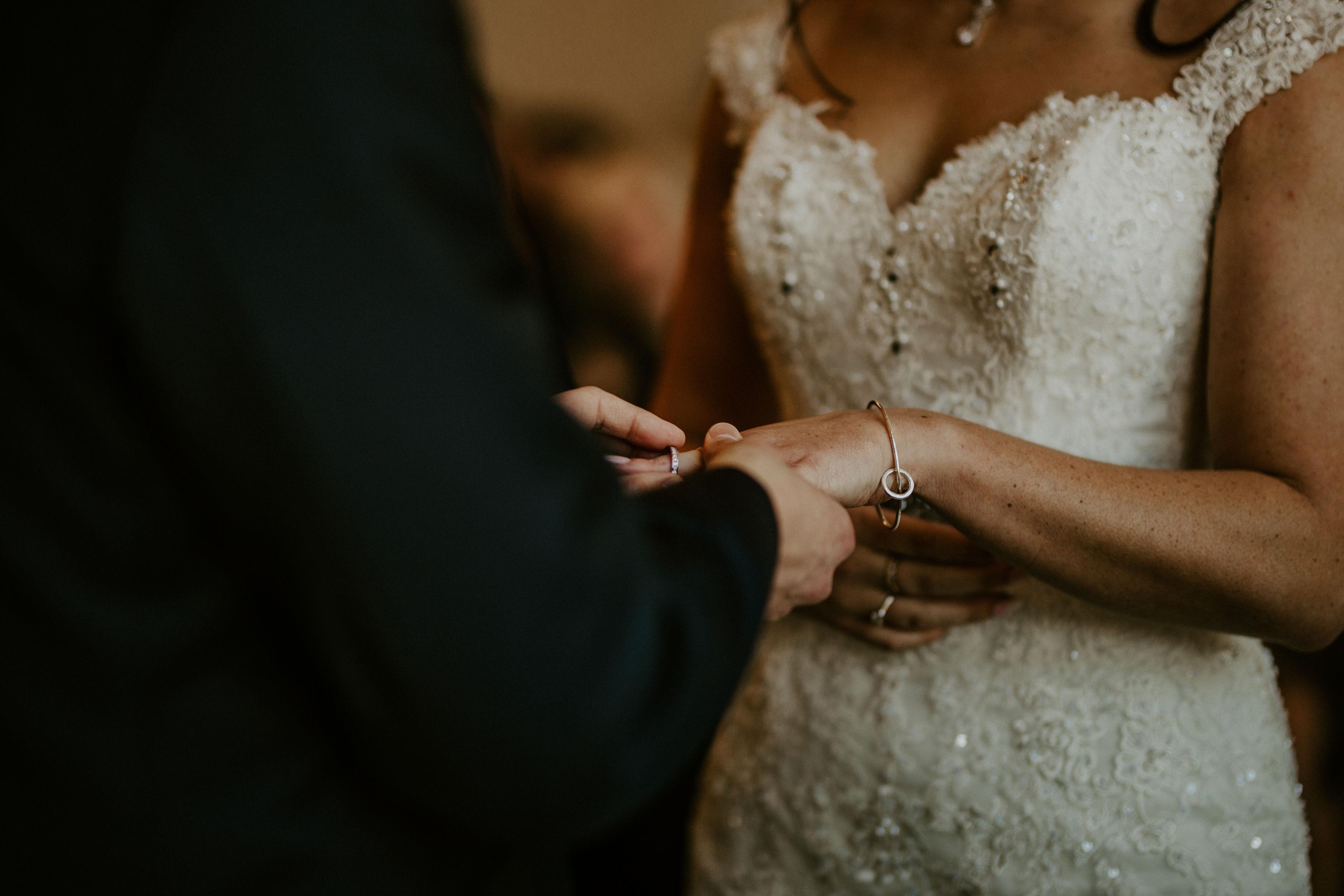 Groom puts brides ring on her finger