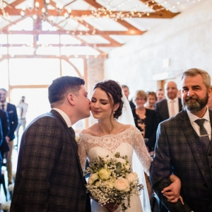 Groom pecks bride on the cheek as her father delivers her