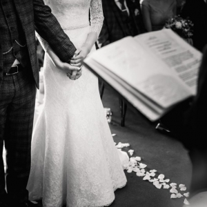 Bride and groom hold hands in front of the registrar