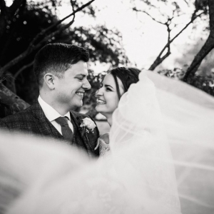 Bride and groom enveloped in her veil