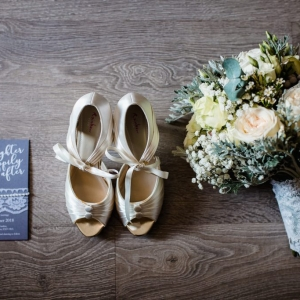 Wedding invitation, brides shoes an bouquet
