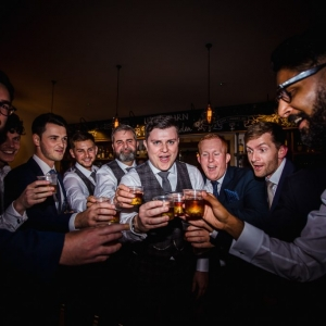 Grooms men toast drinks together