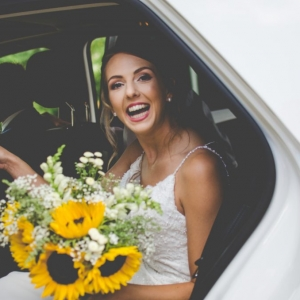 Bride broad smile while exiting the wedding car