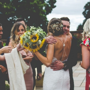 Bride is cuddled by guests