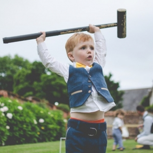 Little boy holds croquet mallet aloft