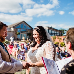 Bride and groom hold hands while exchanging vows