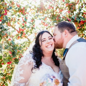 Groom kisse bride under berry laiden tree