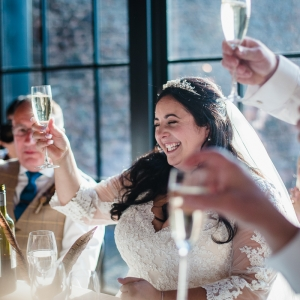 Bride and guests raises glasses to toast