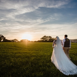 Bride and groom walk in field at sunset