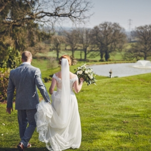 Groom holds brides dress as they walk to the lake
