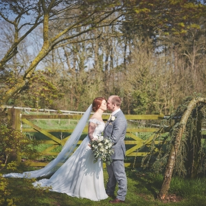 Bridal couple kiss by gate to field