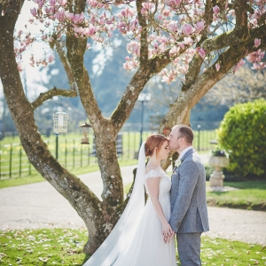 Bride and groom kiss by magnolia tree