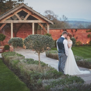 Couple embrace at dusk in the walled garden