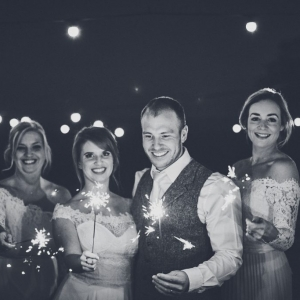Bride and groom with sparklers and wedding guests at night