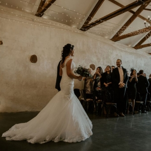Bride walks the aisle in the cider barn