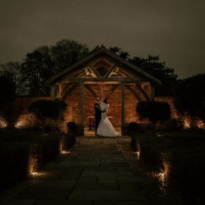 Bride and groom embrace in the arbor in low light