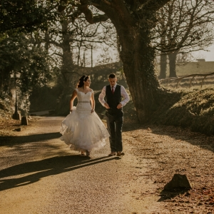 Bride and groom walk up the lane in low light