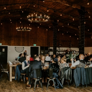 Wedding guests seated at dinner in the stable barn