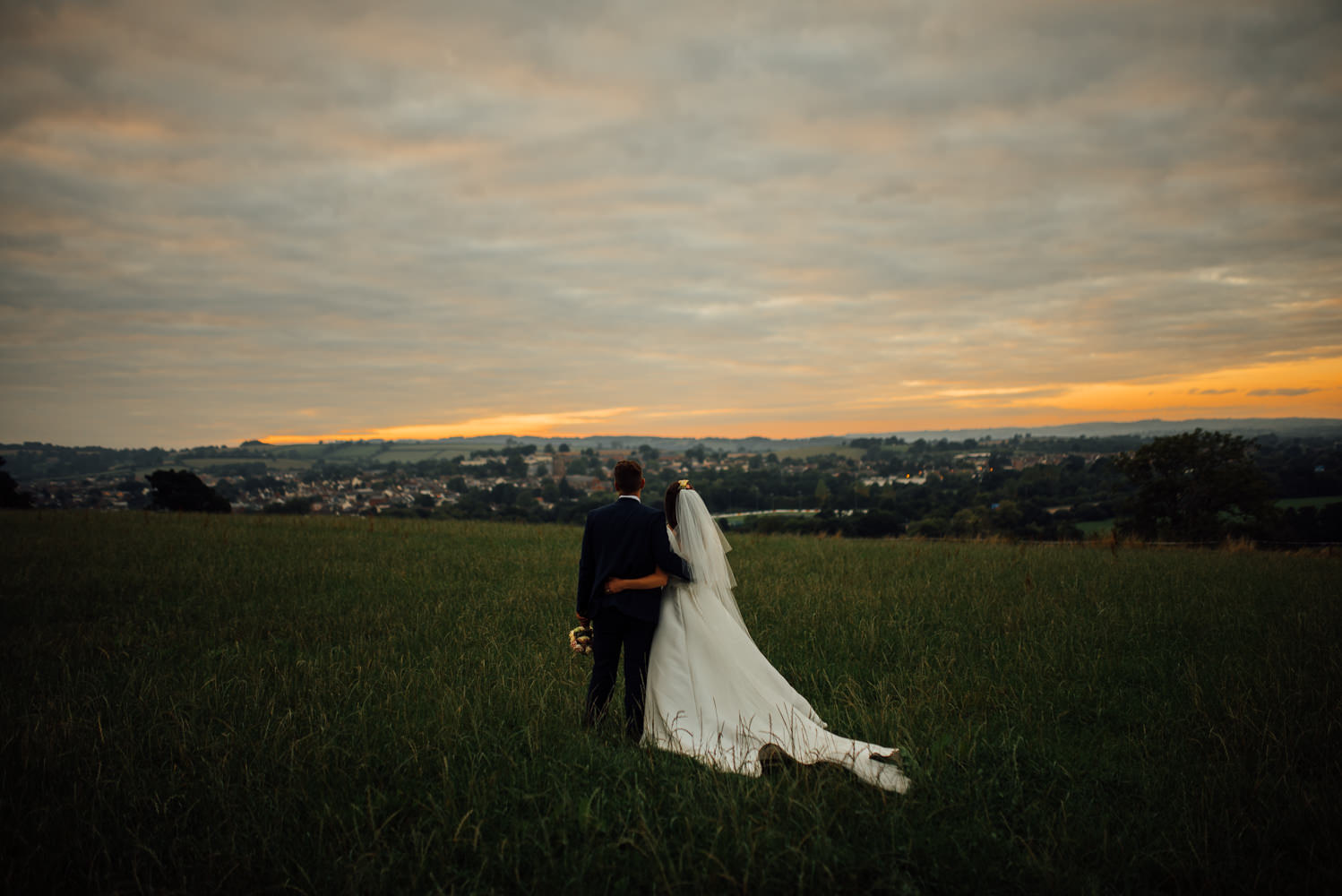 Couple walk in the fields at sunset