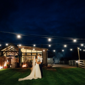 Couple embrace in garden by fire pits