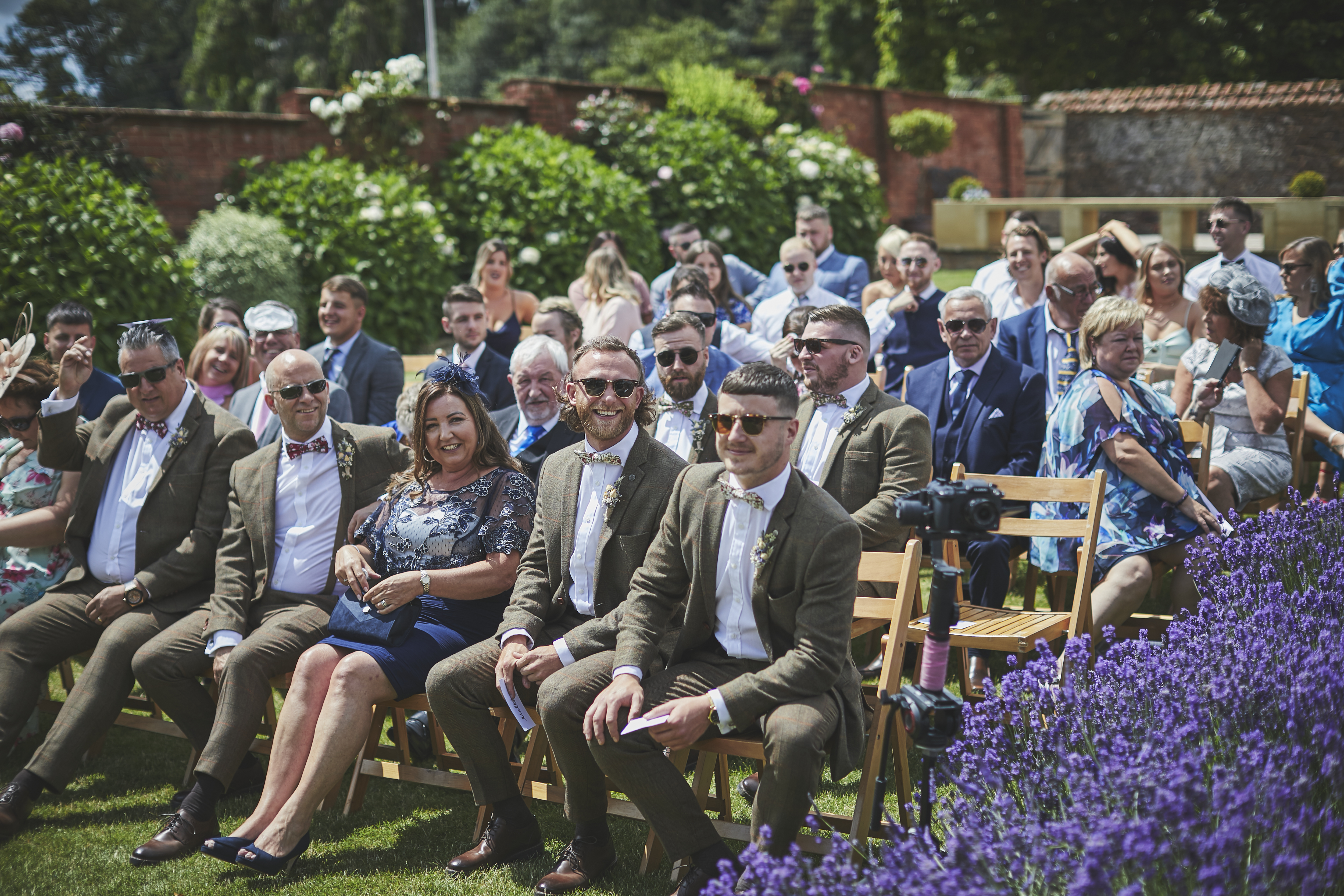 Guests seated in the Walled garden at Upton Barn await arrival of the bride