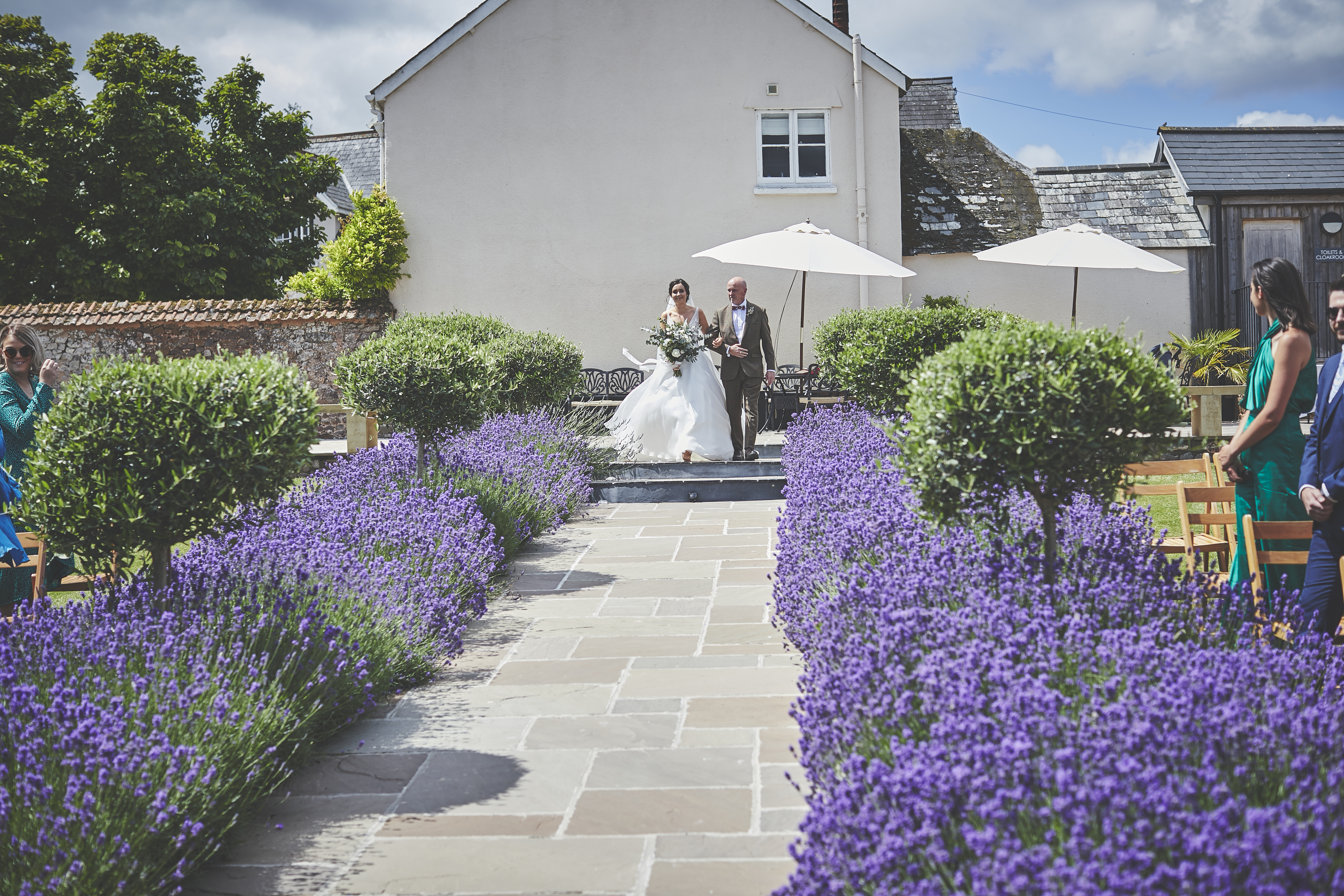 Bride and her Father descend the aisle steps into the walled Garden